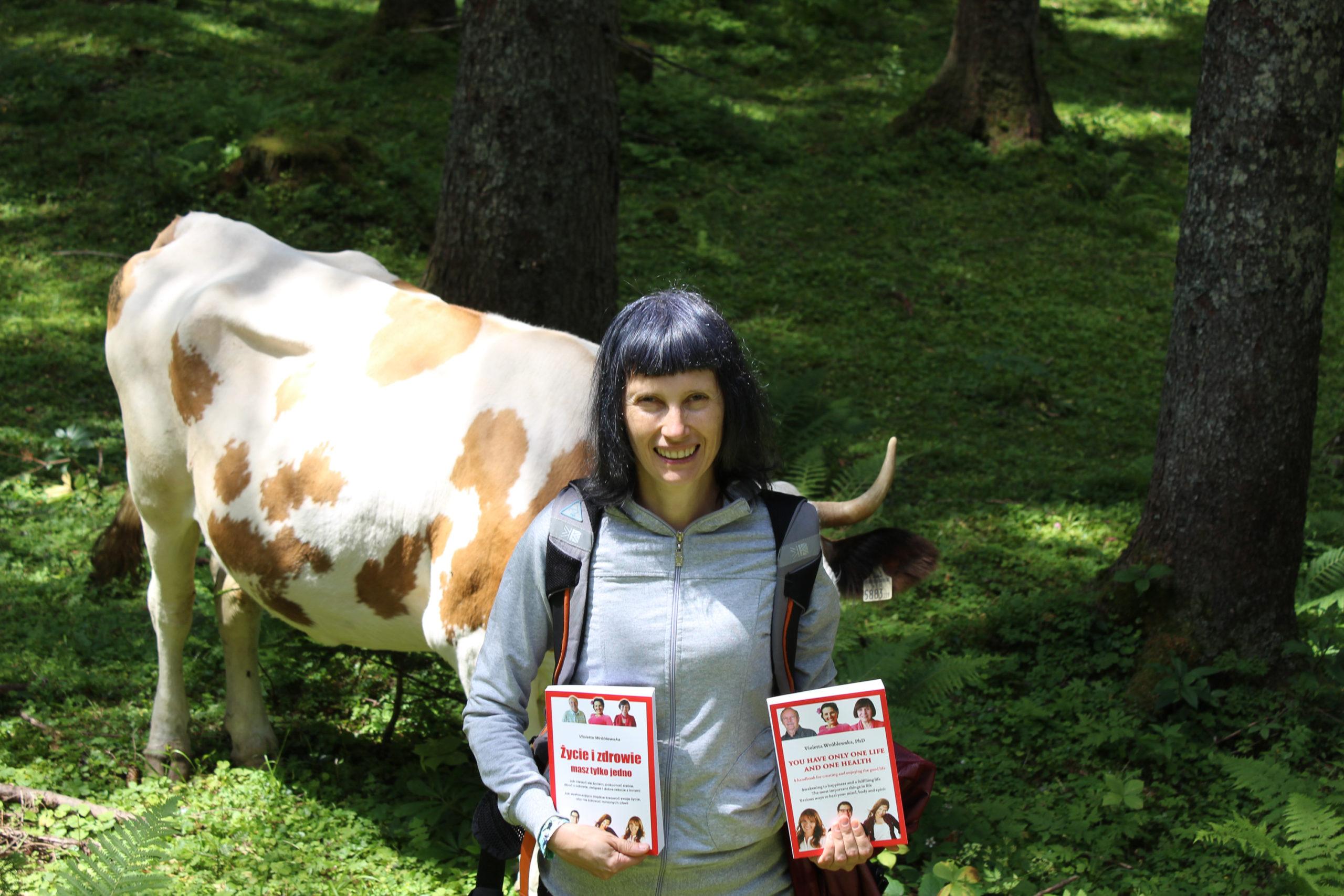 Viola trzyma książki krowa w tle