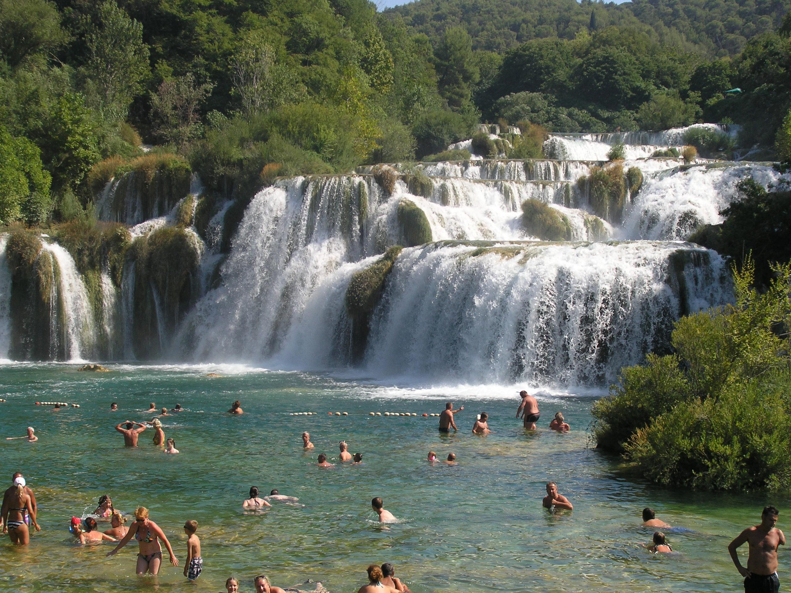 Ludzie kąpiący się na tle wodospadu