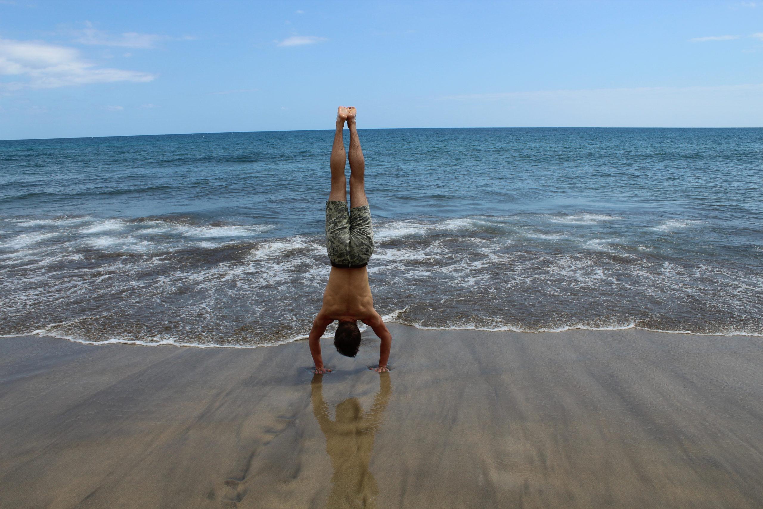 Stoi na rękach na plaży