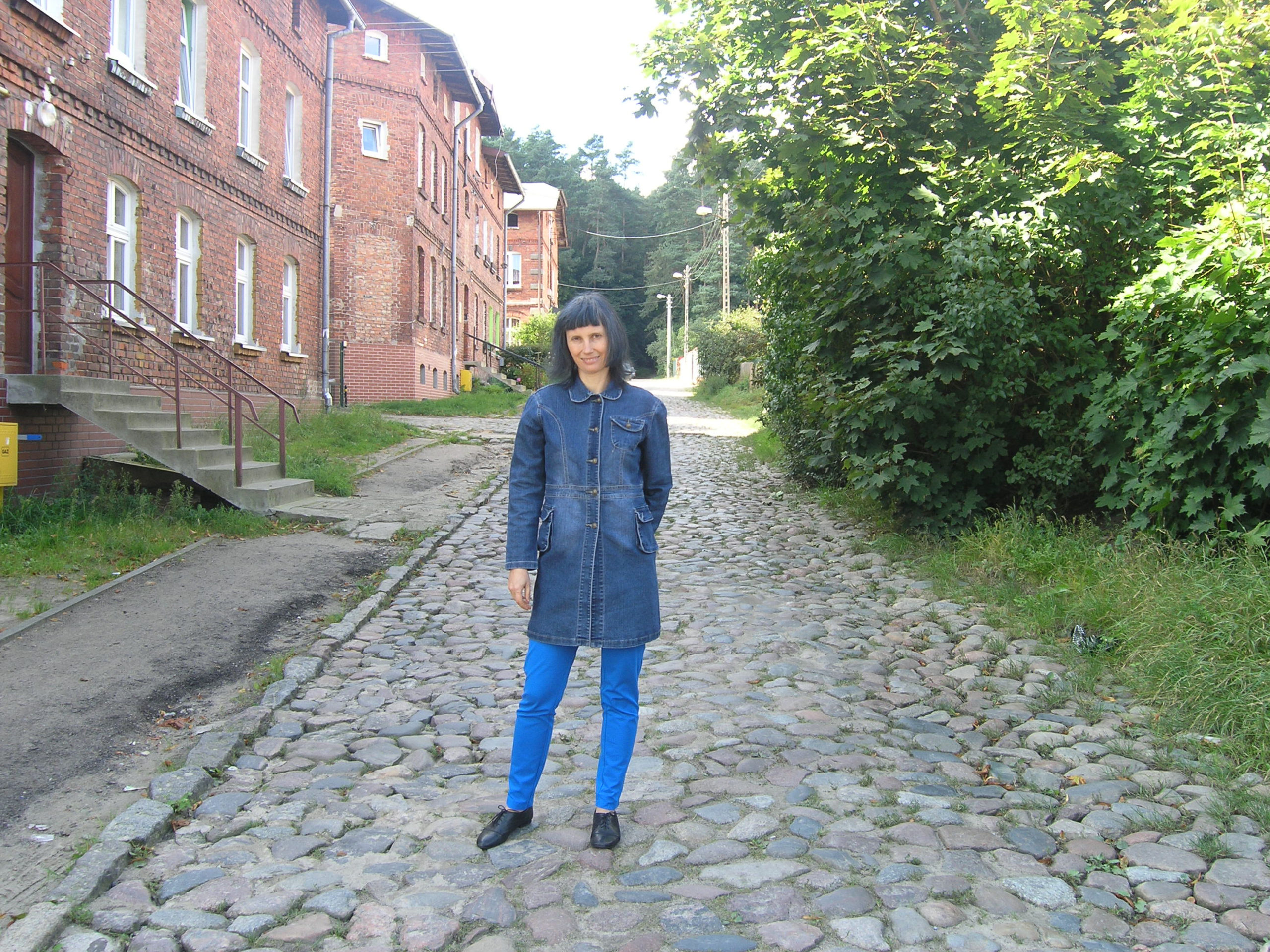 Violetta Wróblewska na tle starych ceglanych budynków