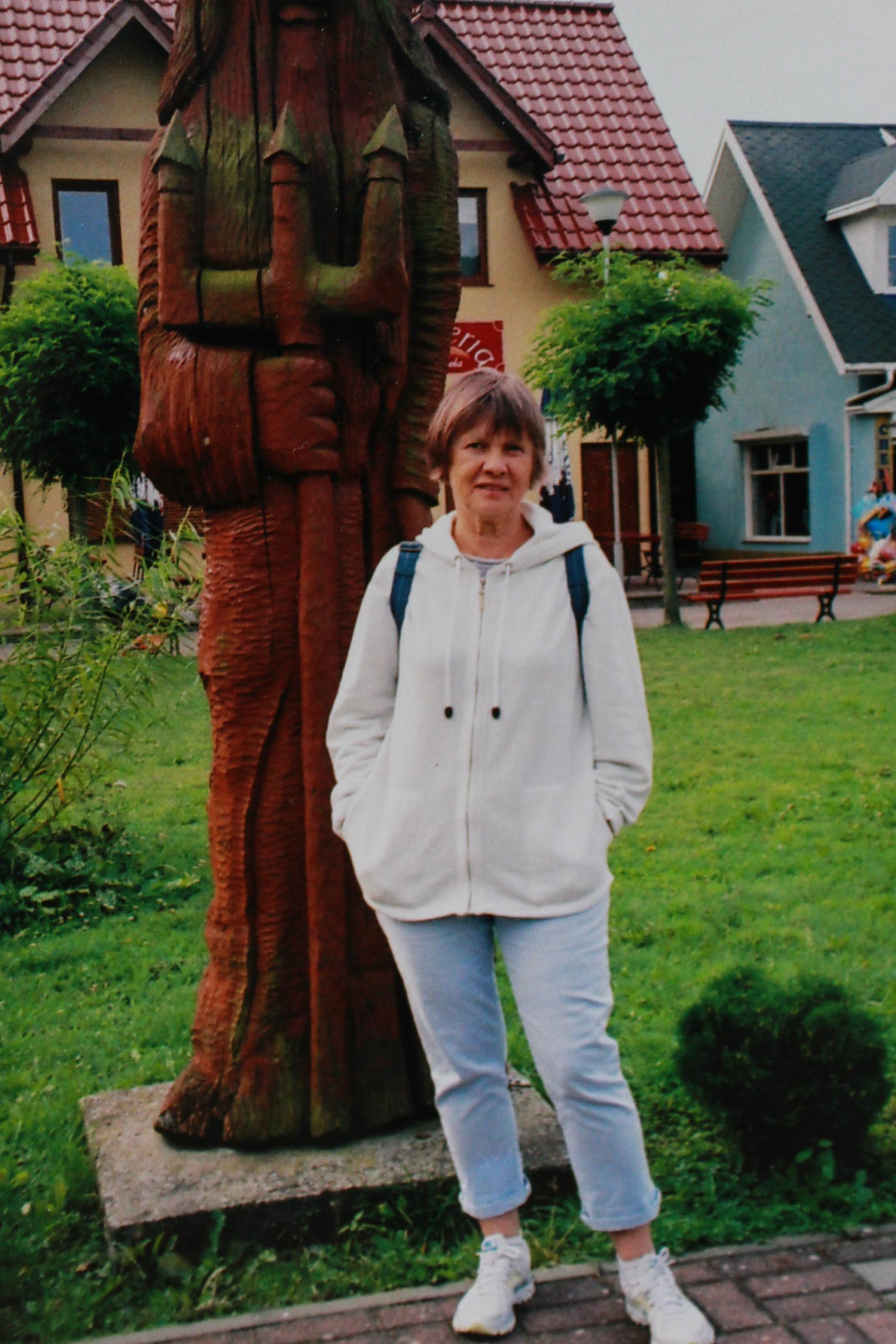 Mama na tle drewnianej rzeźby