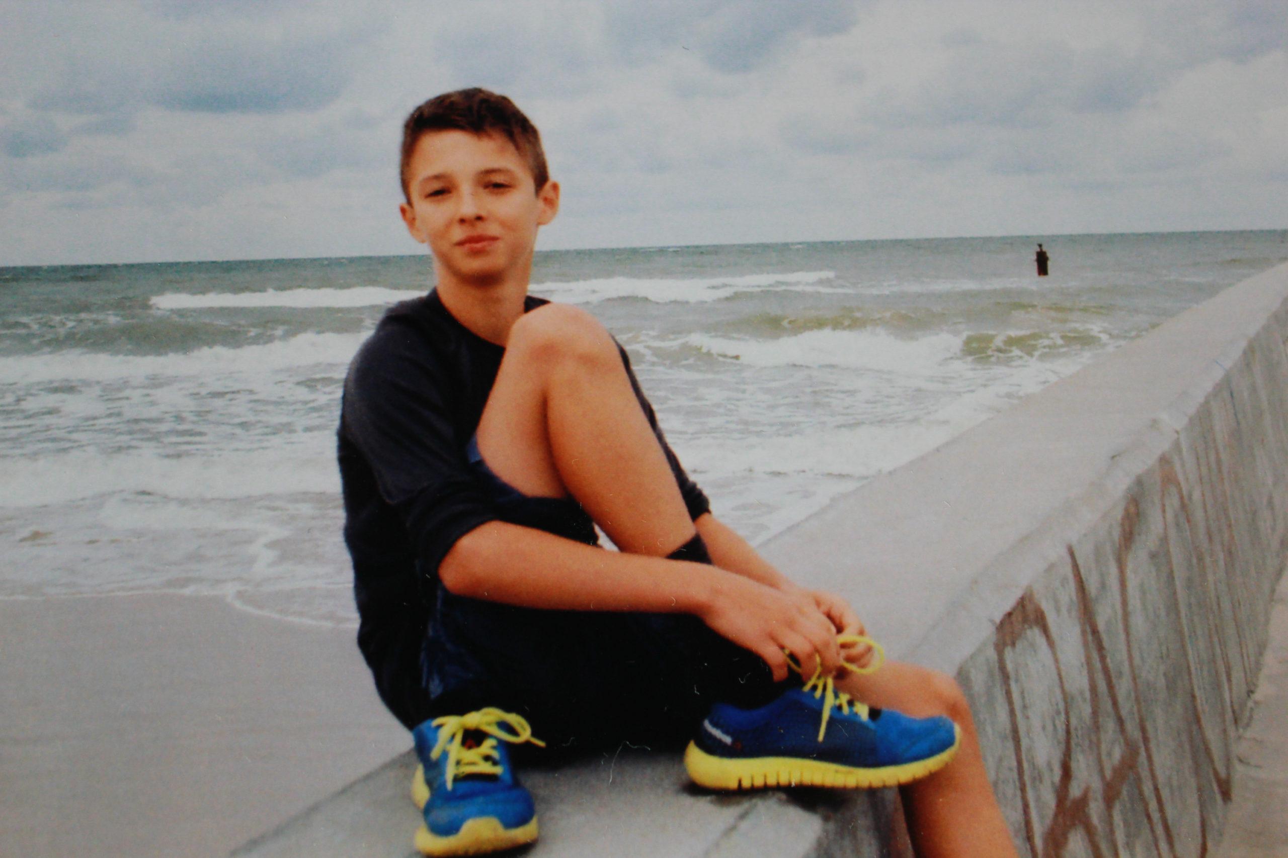 syn zakłada buty nad morzem