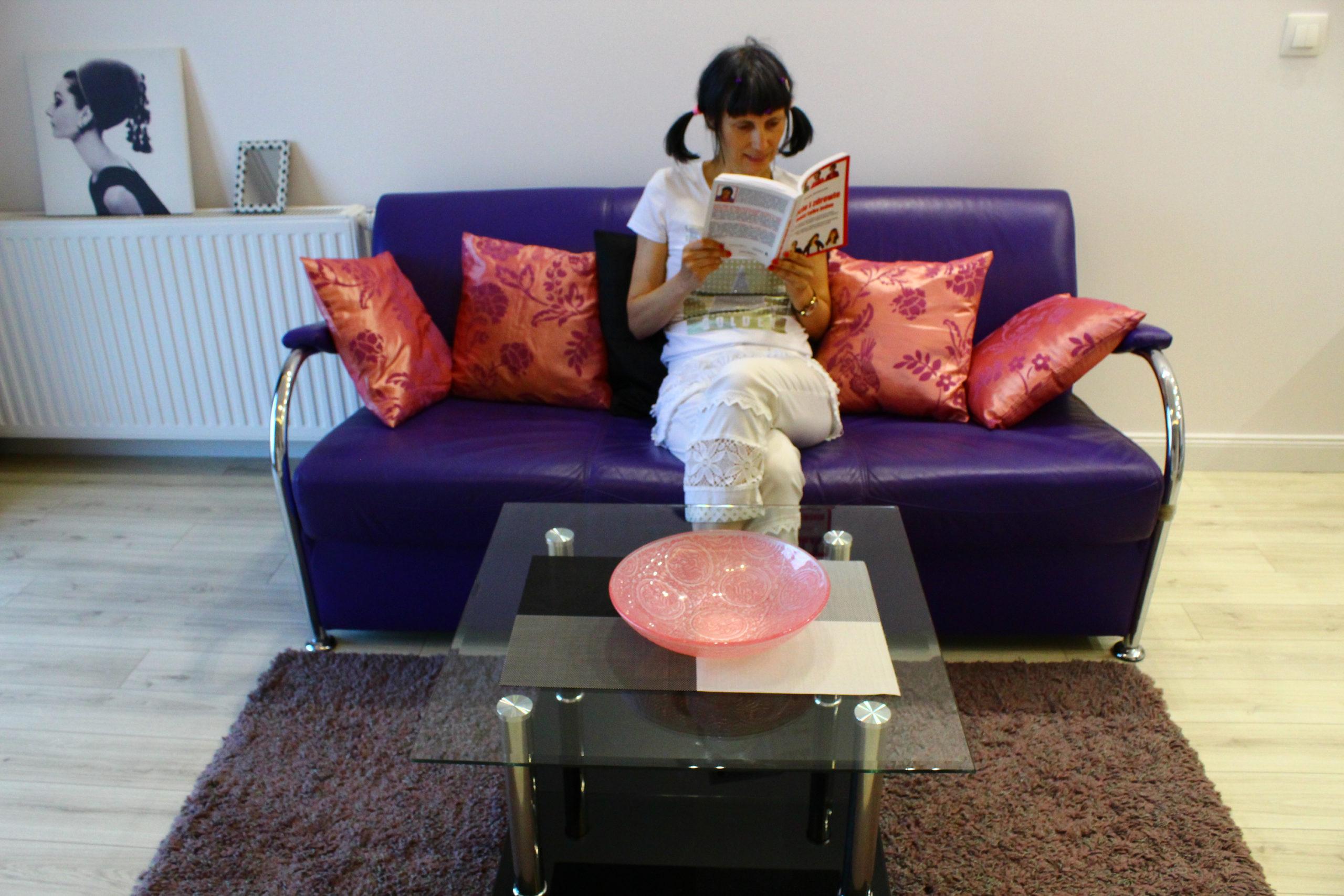 Viola czyta książkę na fioletowej kanapie
