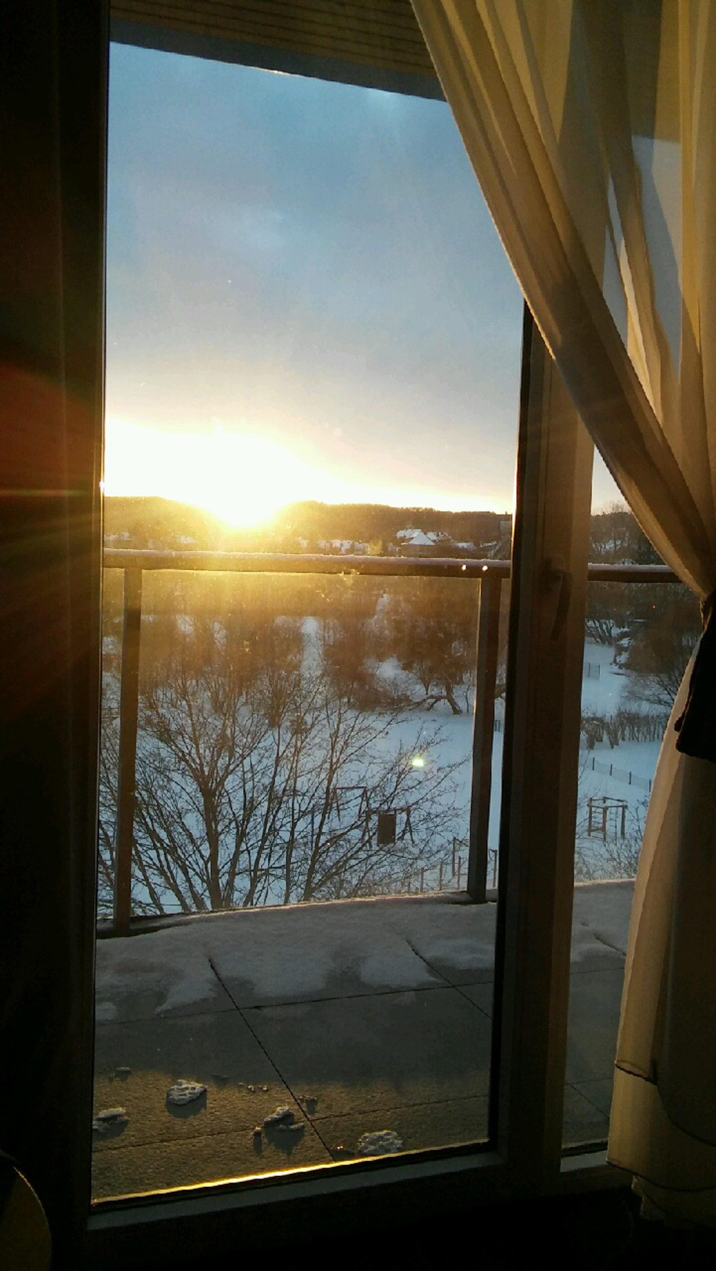 widok na zachodzące słońce z okna hotelu