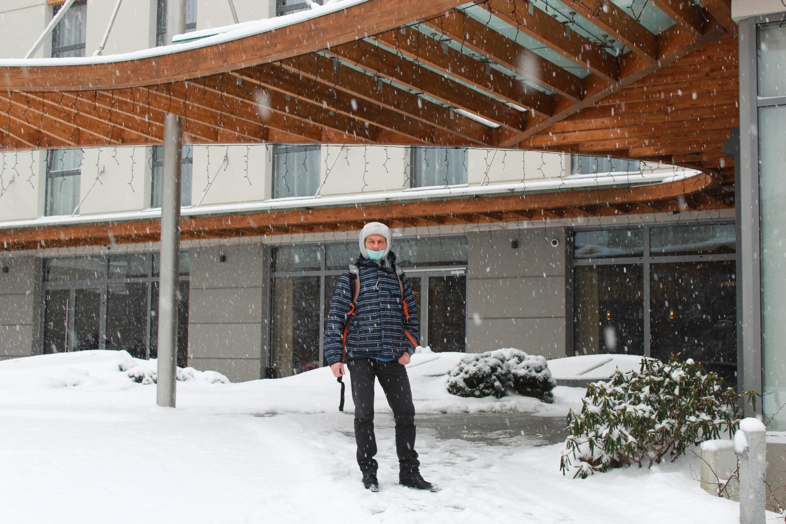mężczyzna w zimowym ubraniu przed wejściem do hotelu, pada śnieg