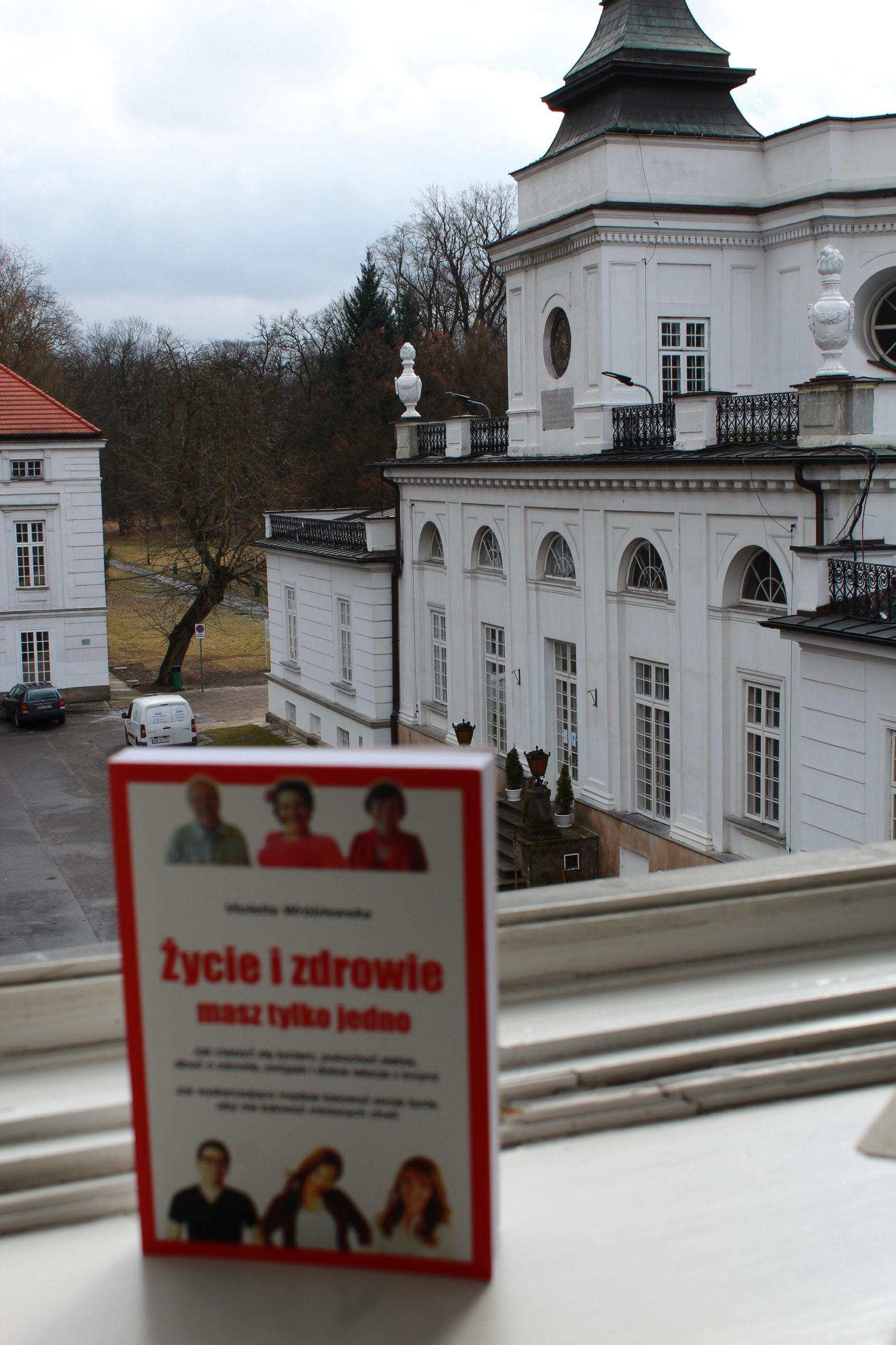 książka a w tle pałac